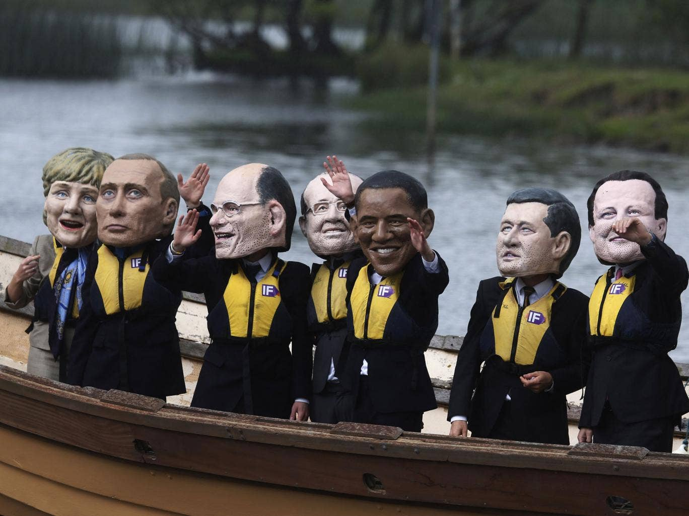 Anti-hunger activists wear giant head masks depicting the G8 leaders