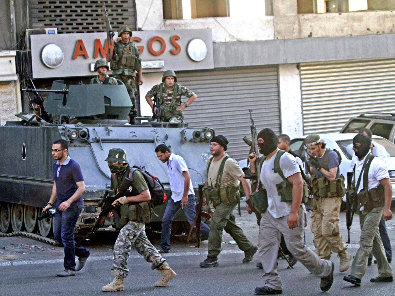 Gunmen and followers of hardline Sunni cleric Sheik Ahmad al-Assir pass in front of Lebanese army soldiers in the southern port city of Sidon