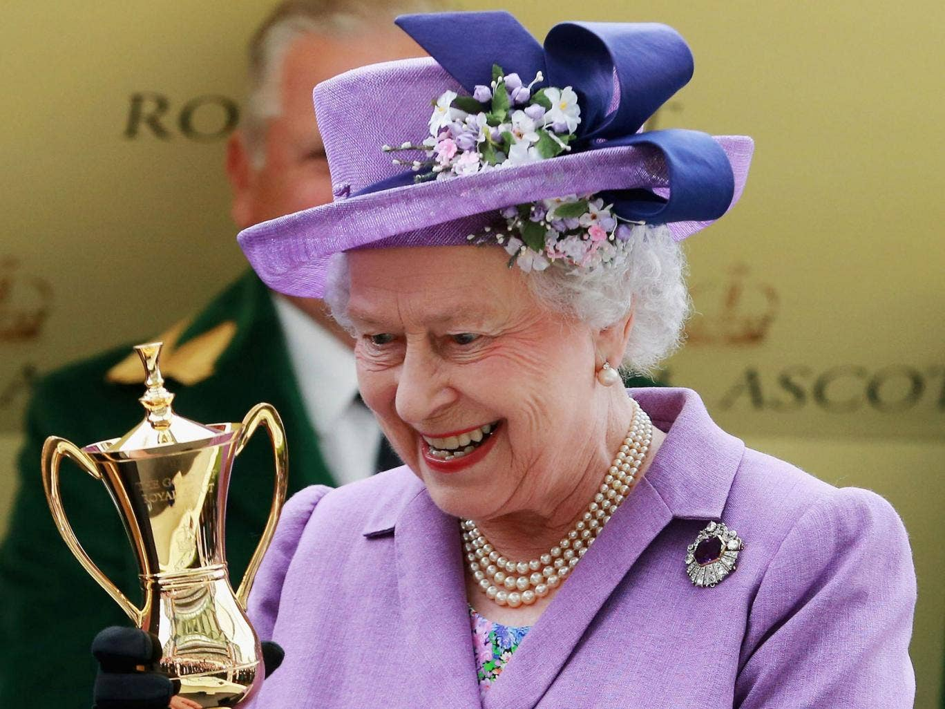 The Queen is handed the Gold Cup at Ascot yesterday after victory for her horse, Estimate