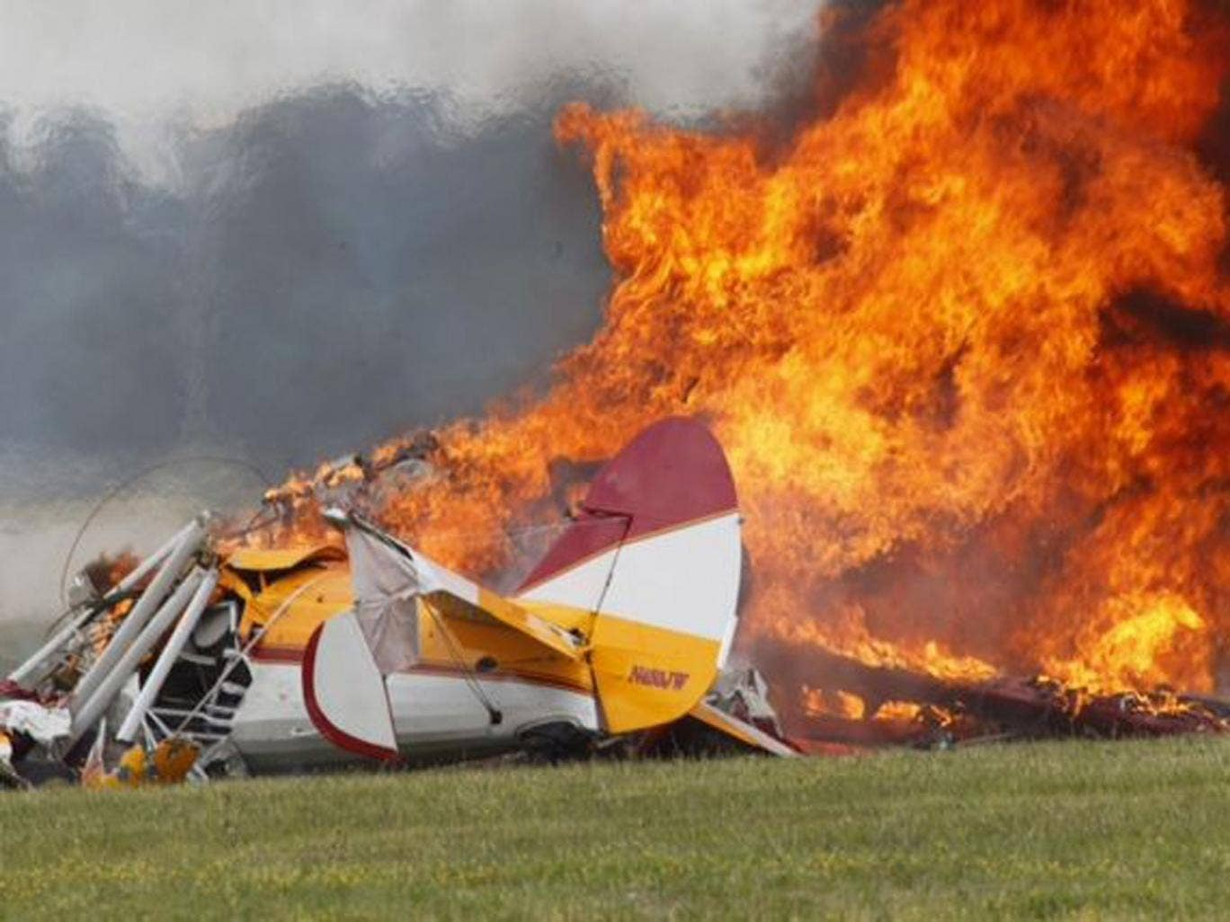 Flames erupt from a plane after it crashed at the Vectren Air Show at the airport in Dayton, Ohio
