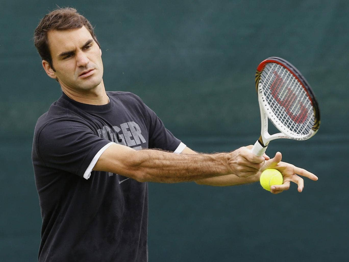 Defending Wimbledon champion, the Swiss Roger Federer plays a return during a training session