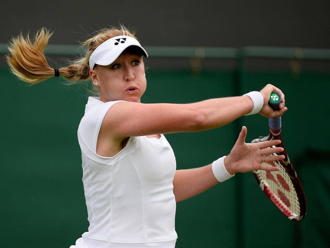 Elena Baltacha of Great Britain hits a forehand during the Ladies Singles match against Flavia Pennetta of Italy on day one at Wimbledon