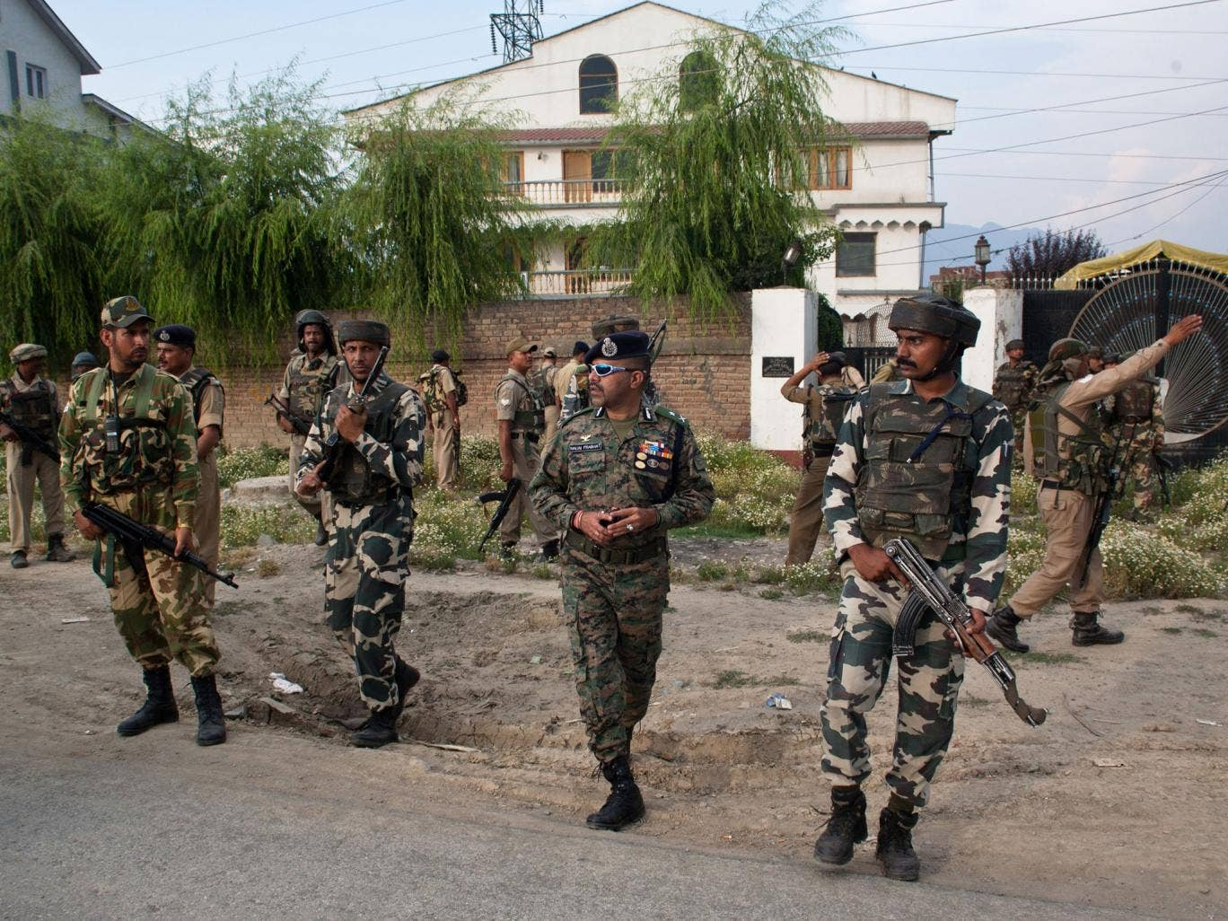 Indian policemen and paramilitary forces search for militants in residential houses after a militant attack on Indian army