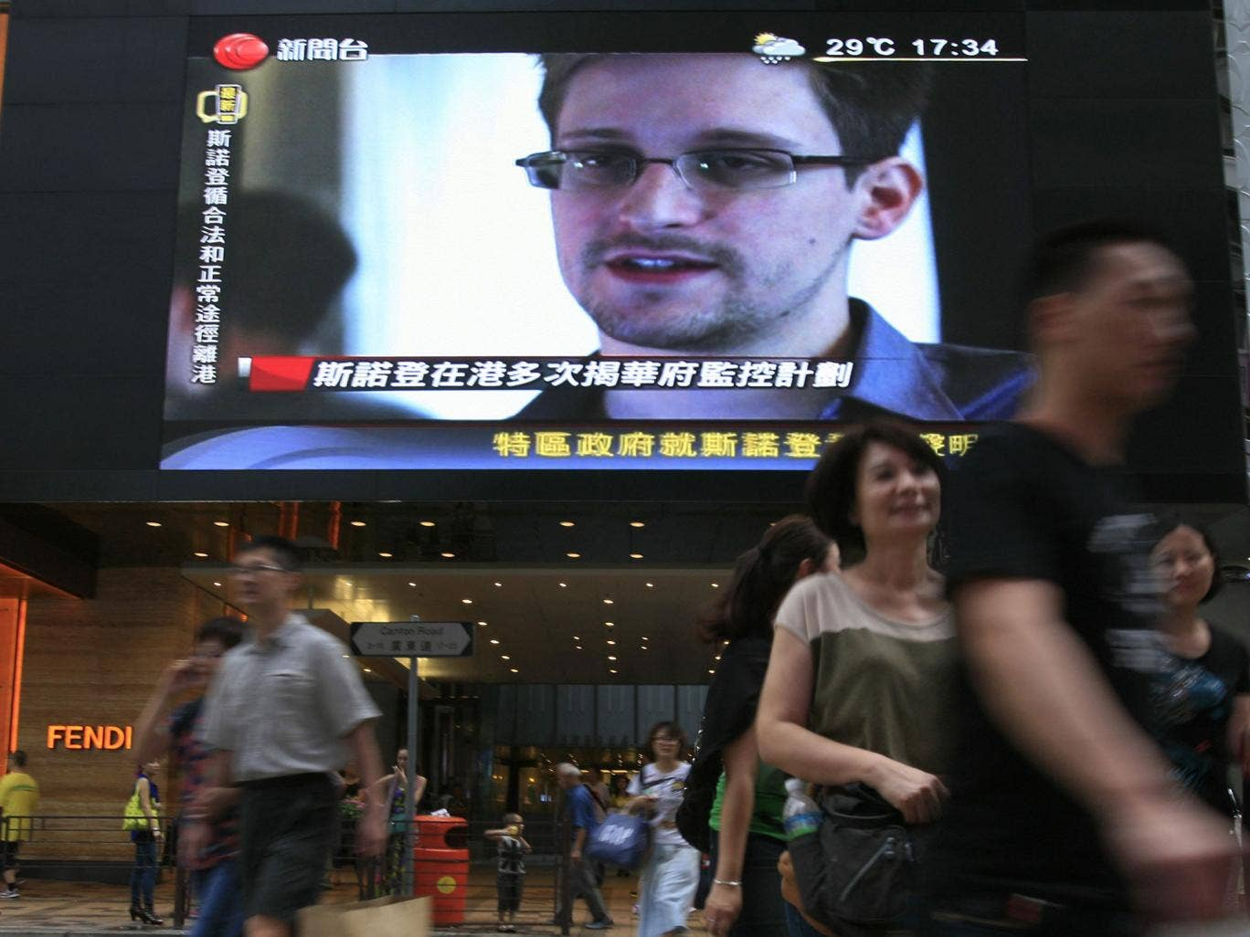 A TV screen shows a news report about Edward Snowden in Hong Kong