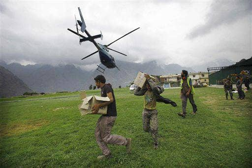 Indian civilians get ready to load relief material for flood affected victims on a helicopter at a makeshift helipad at Joshimath, in northern Indian state of Uttarakhand