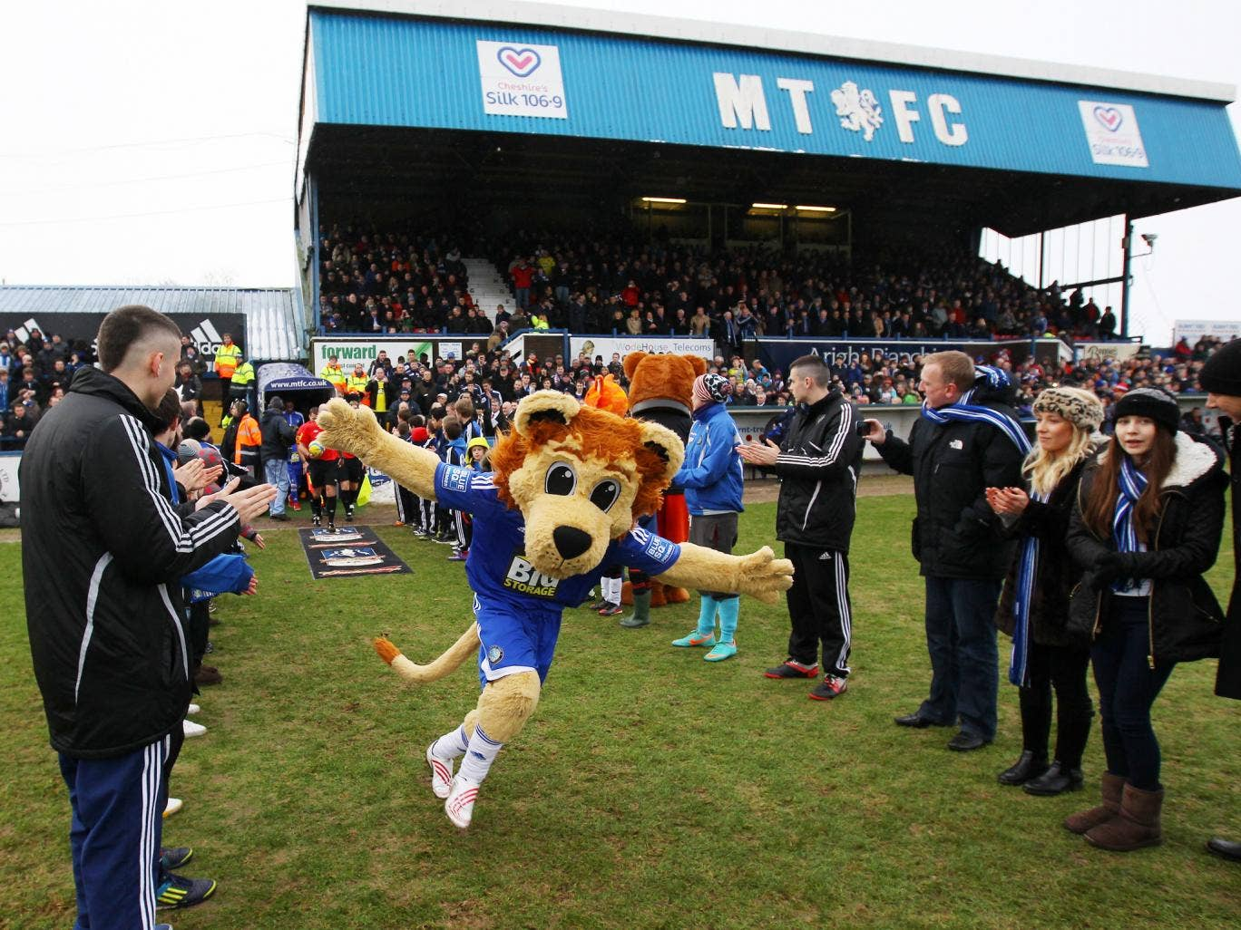 Mascot Roary the Lion leads the teams out ahead at Macclesfield - but the club has dropped plans for a fan to pay for a game