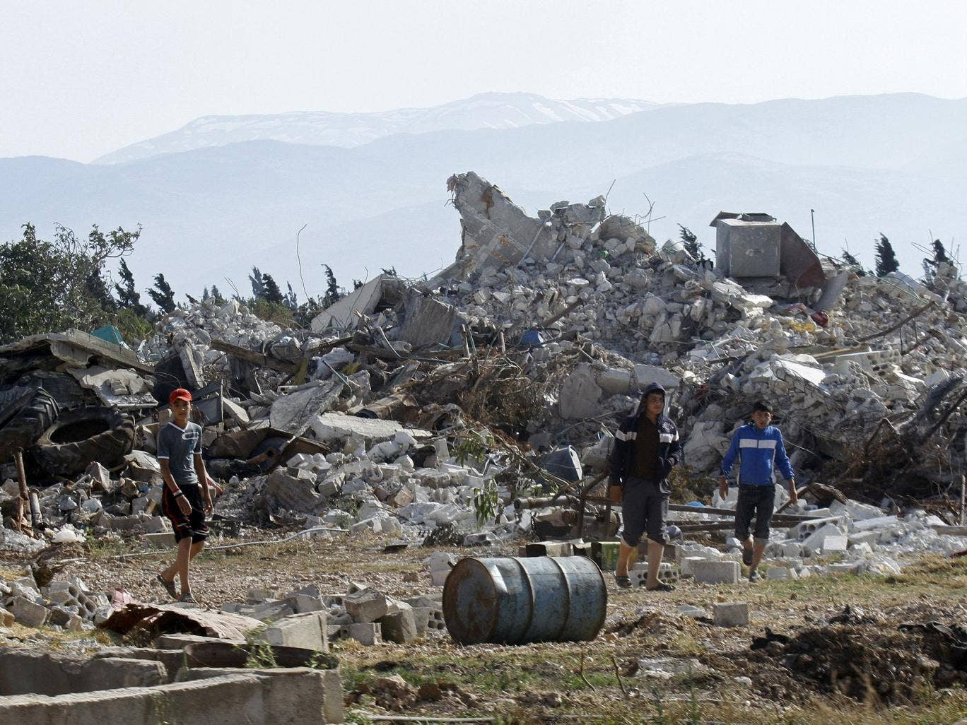 Syrian youths walk amongst the rubble in the village of al-Hamidiyeh, north of Qusayr, in Homs province