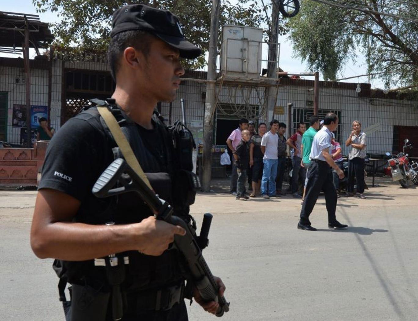Armed police patrol the road leading into Lukqun