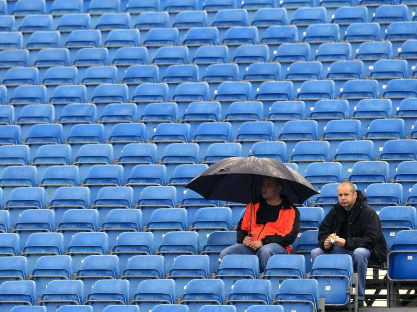 Spectators sit in the rain during the first practice session at the Silverstone circuit