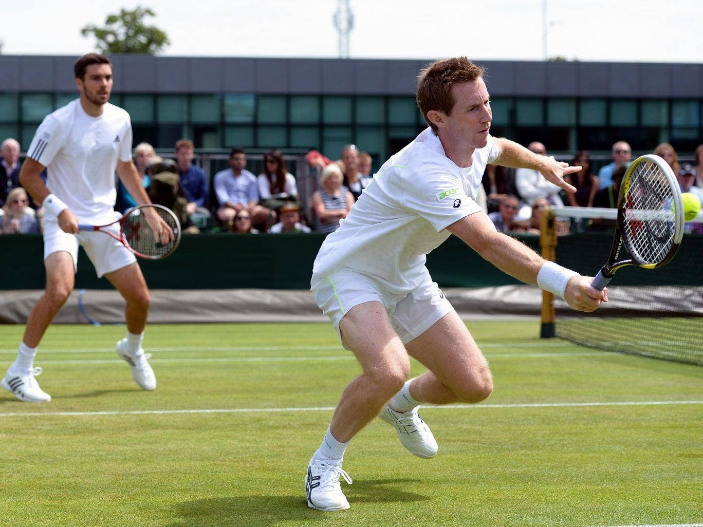 Grass master: Jonny Marray hits a volley in his doubles win
