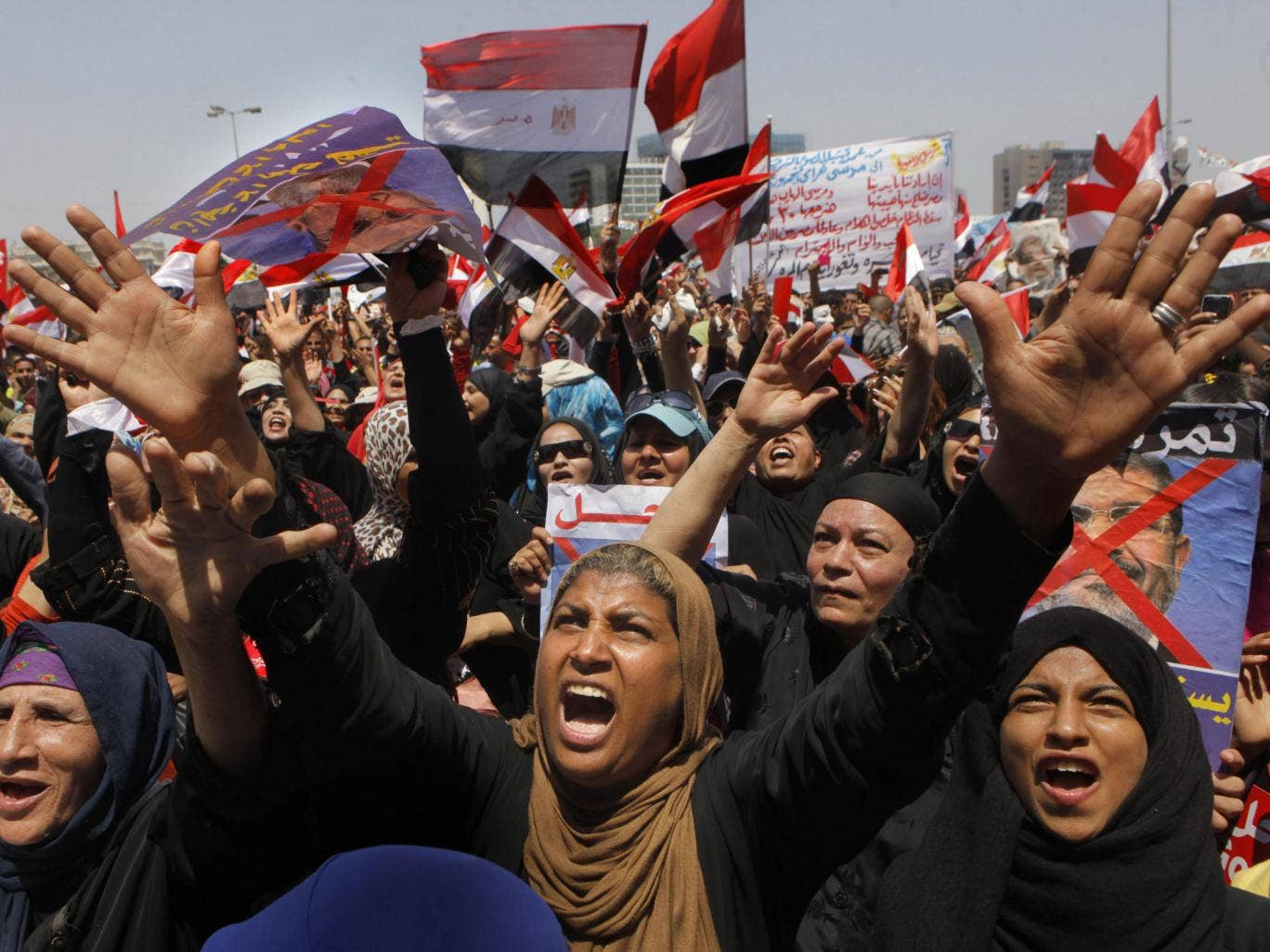 Protesters chant and hold anti-President Morsi posters during a rally in Cairo's Tahrir Square