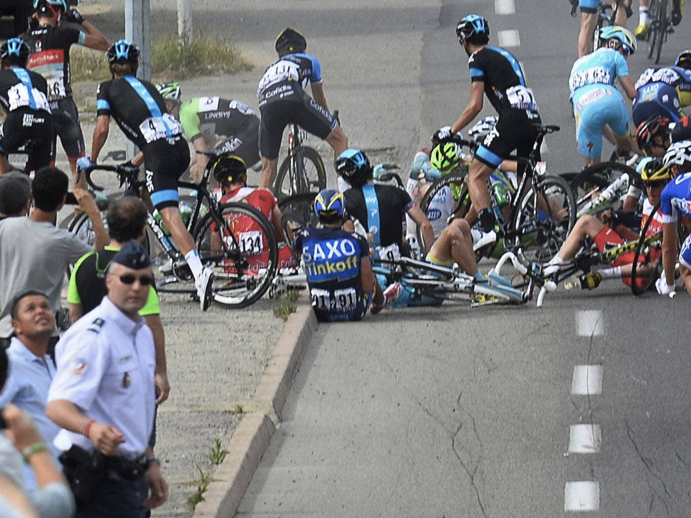 Alberto Contador (no 91) sits on the road after the crash