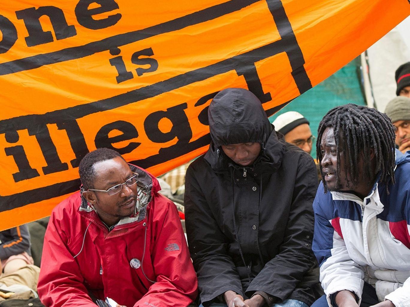 Asylum seekers sit in an outdoor camp in Munich
