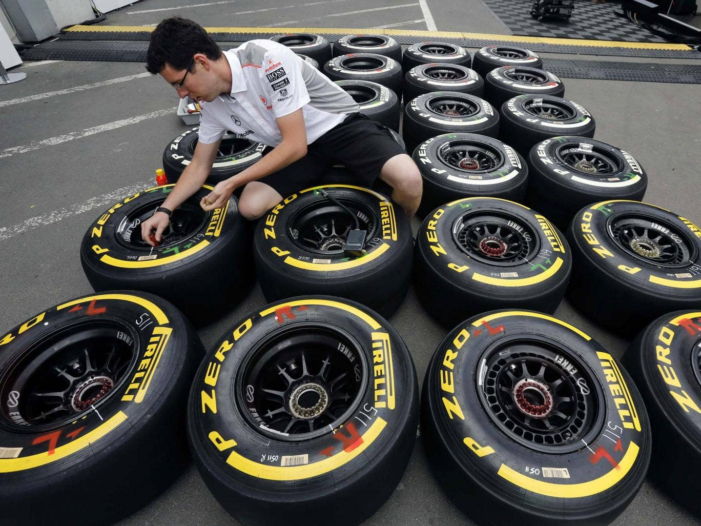 An engineer checks the new Kevlar-enforced rear tyres of McLaren drivers Sergio Perez and Jenson Button in preparation for the German Grand Prix at the Nürburgring
