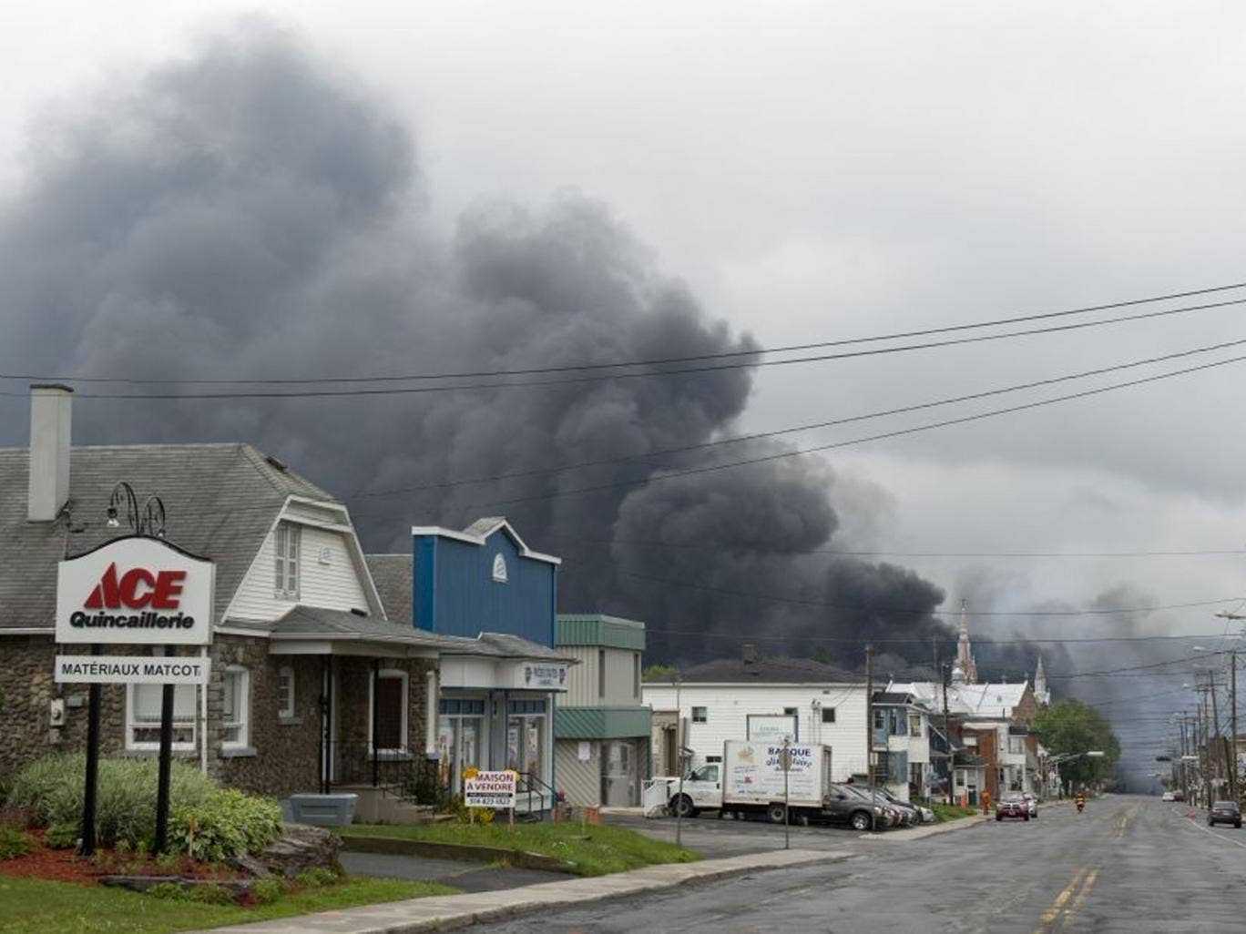 Smoke rises from railway cars that were carrying crude oil after derailing in downtown Lac Megantic, Quebec, Canada (AP)
