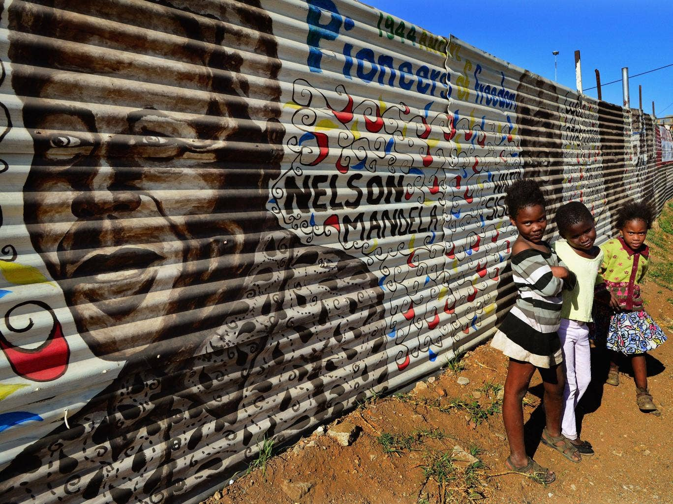 Children in Soweto in front of a mural of Nelson Mandela