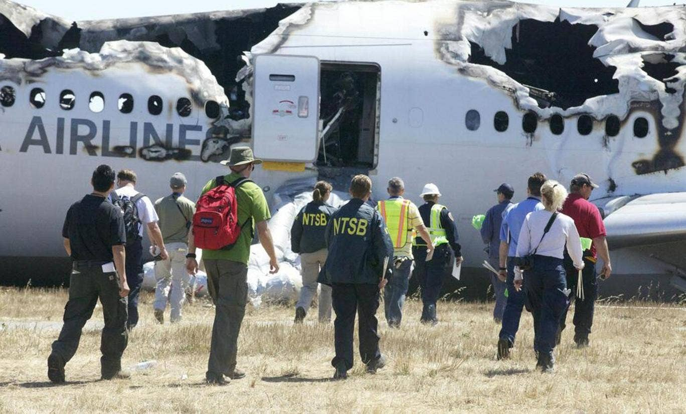 U.S. National Transportation Safety Board (NTSB) investigators work at the scene of the Asiana Airlines Flight 214 crash site at San Francisco International Airport in San Francisco, California