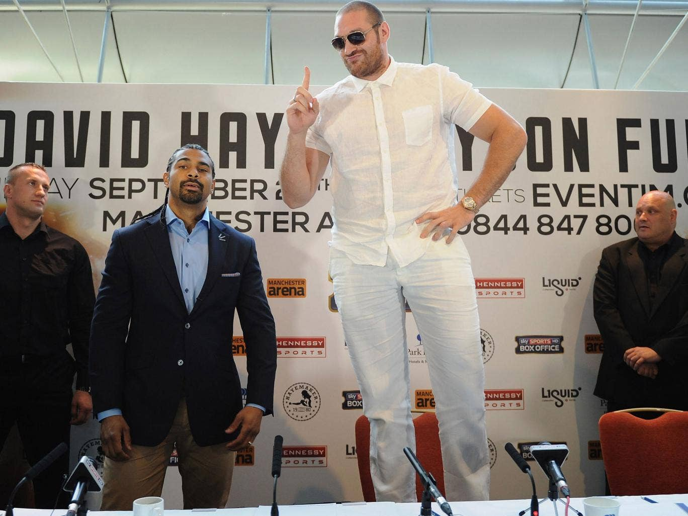Tyson Fury stands on a chair to make a point during his press conference with David Haye