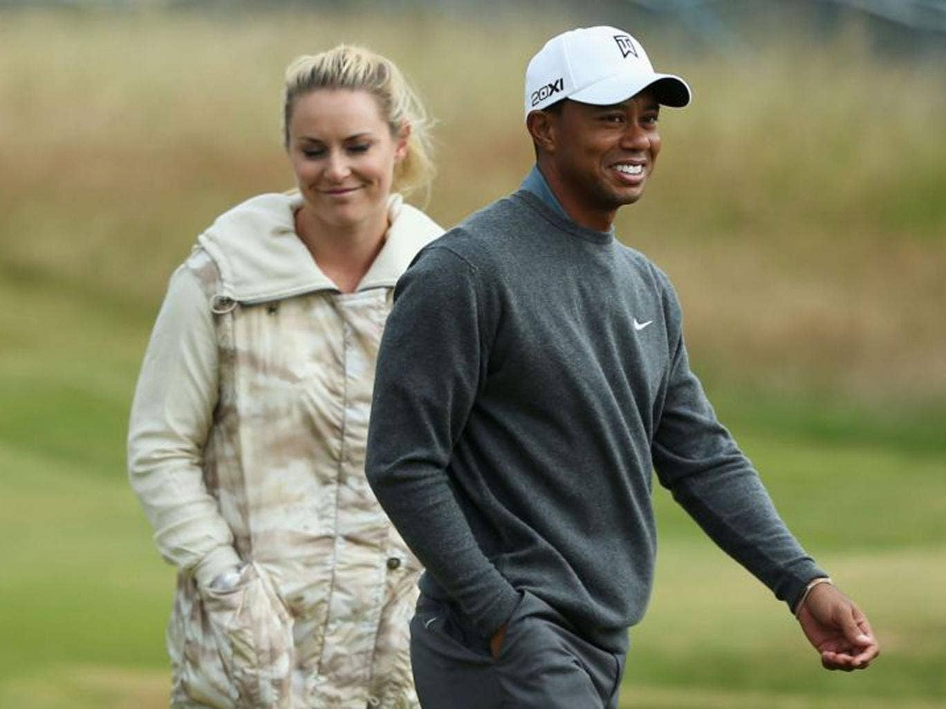 Tiger Woods and his partner, the skiier Lindsey Vonn, are all smiles as they walk the course ahead of this week's Open at Muirfield