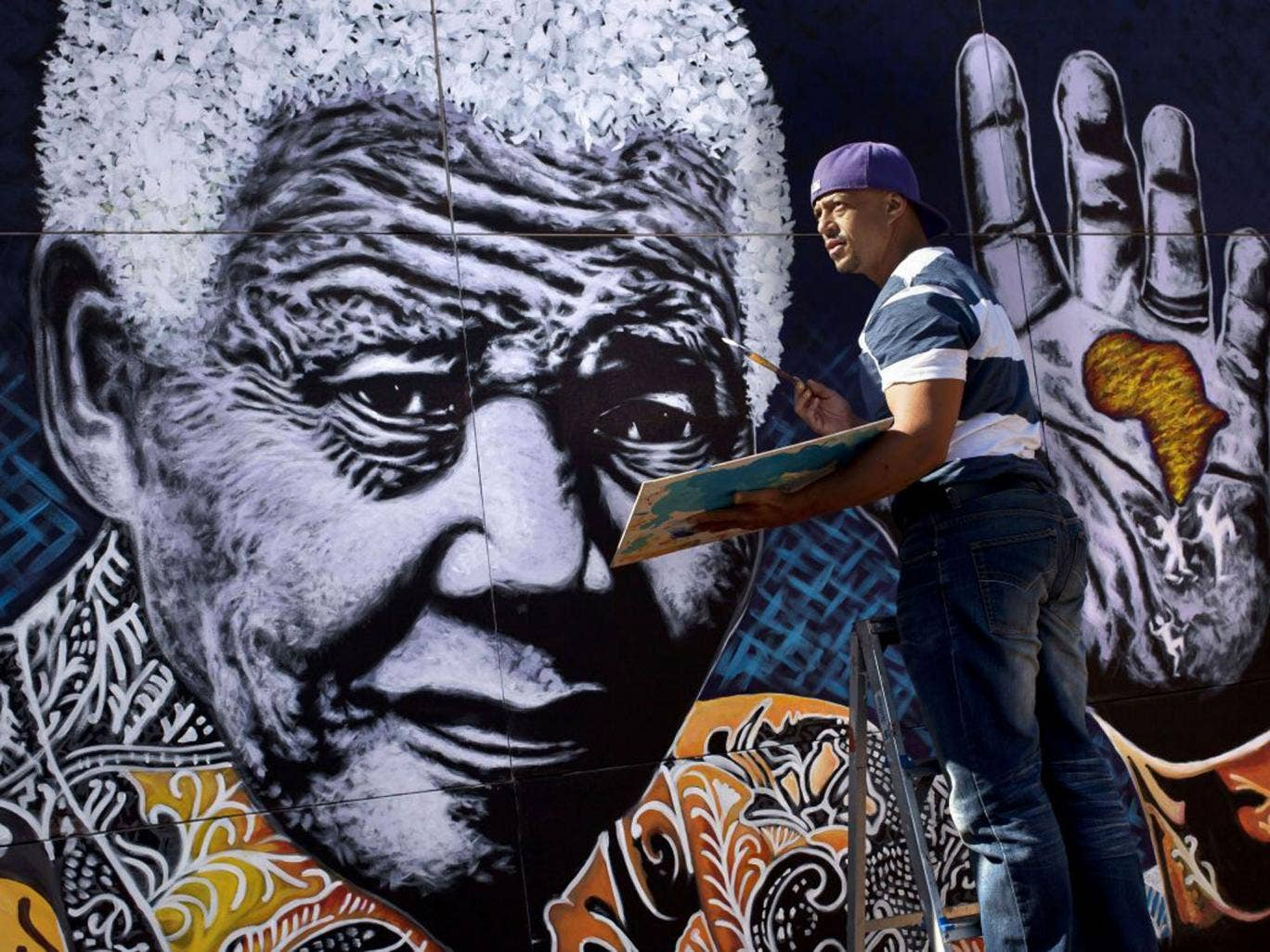 The artist John Adams puts the finishing touches to a giant acrylic on canvas painting of Nelson Mandela outside his house in a suburb of Johannesburg on Monday