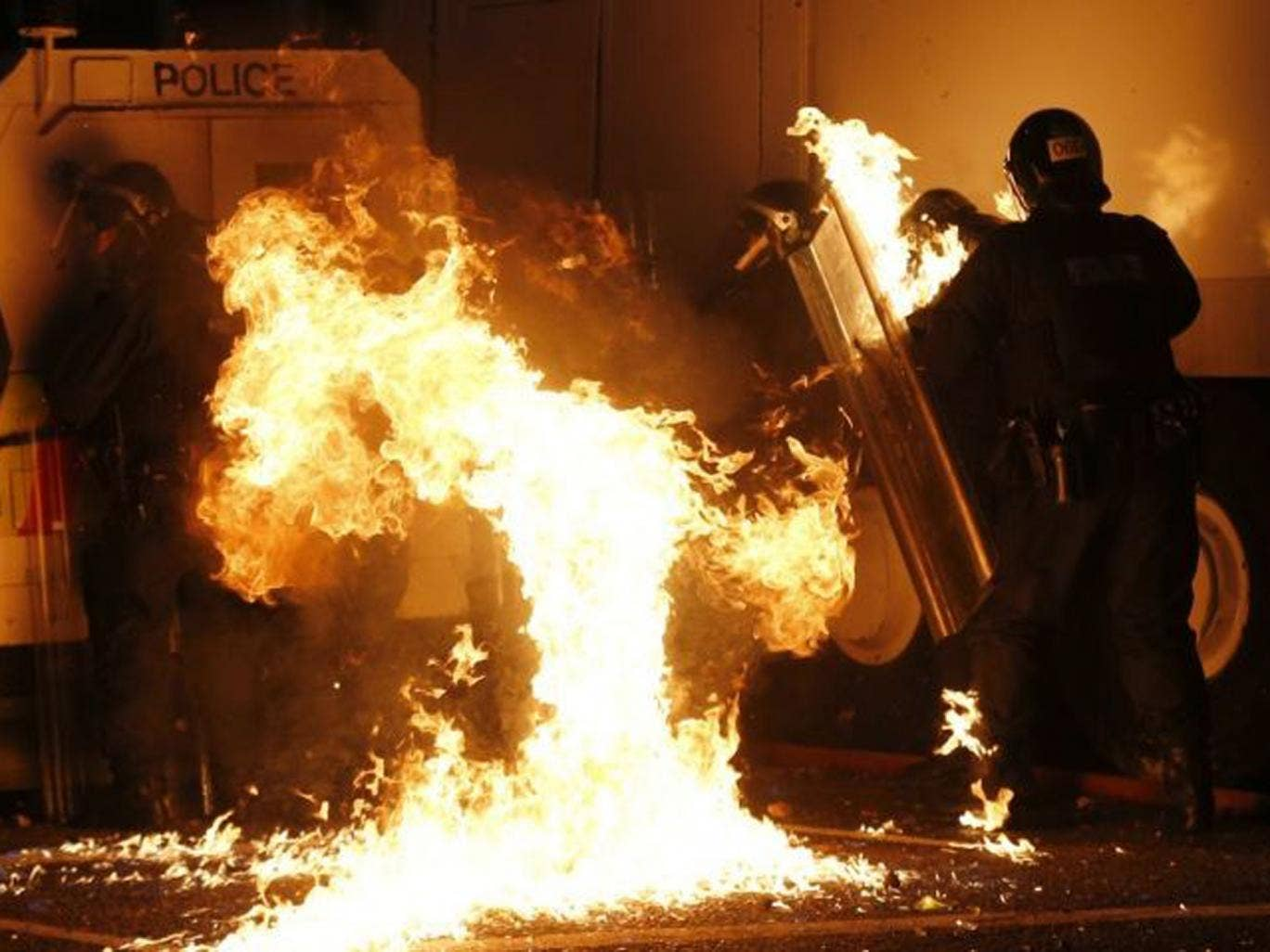 Police shelter from a petrol bomb thrown at them during disturbances on Saturday night