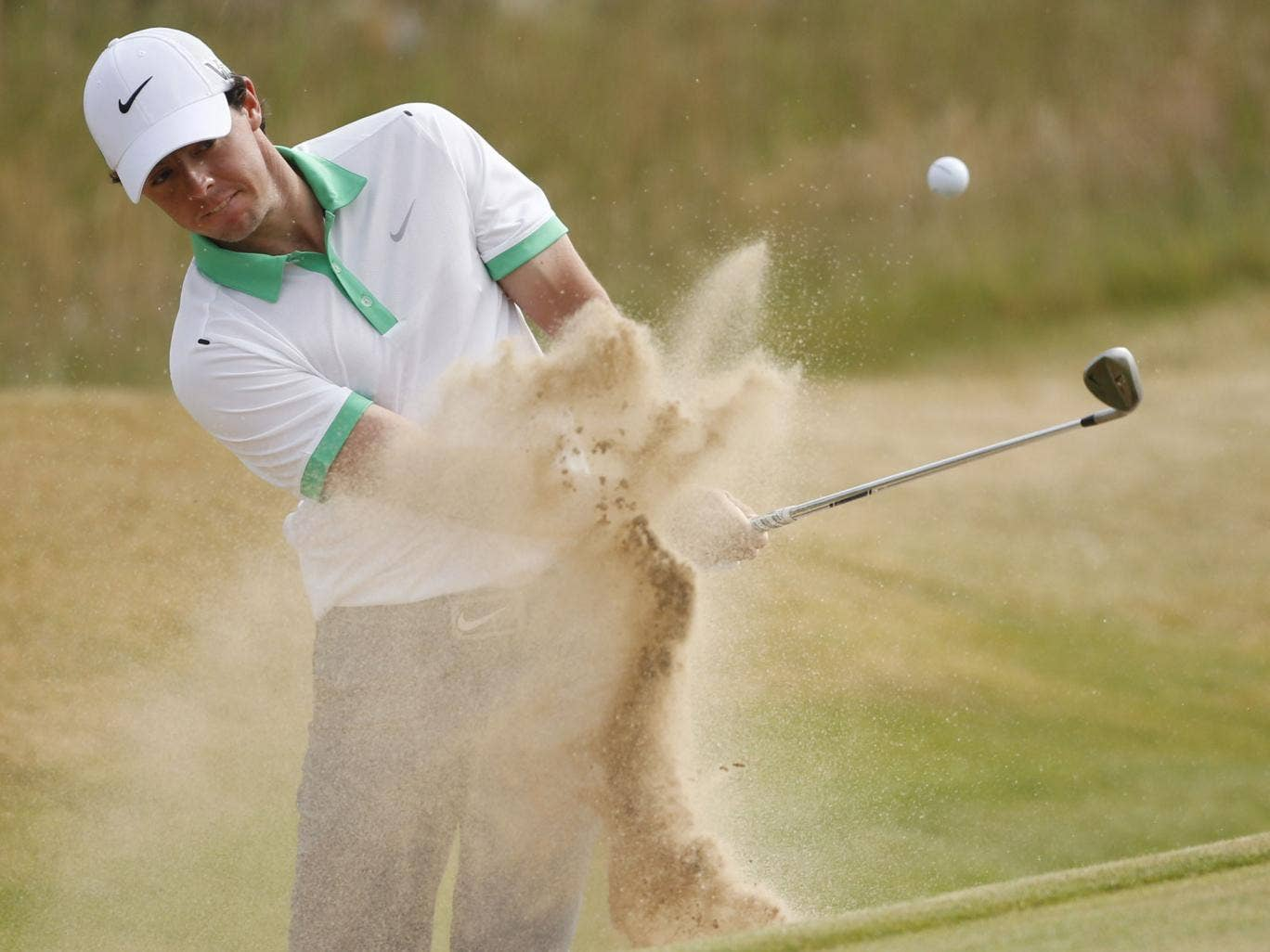 Rory McIlroy plays out of a bunker on to the first green yesterday