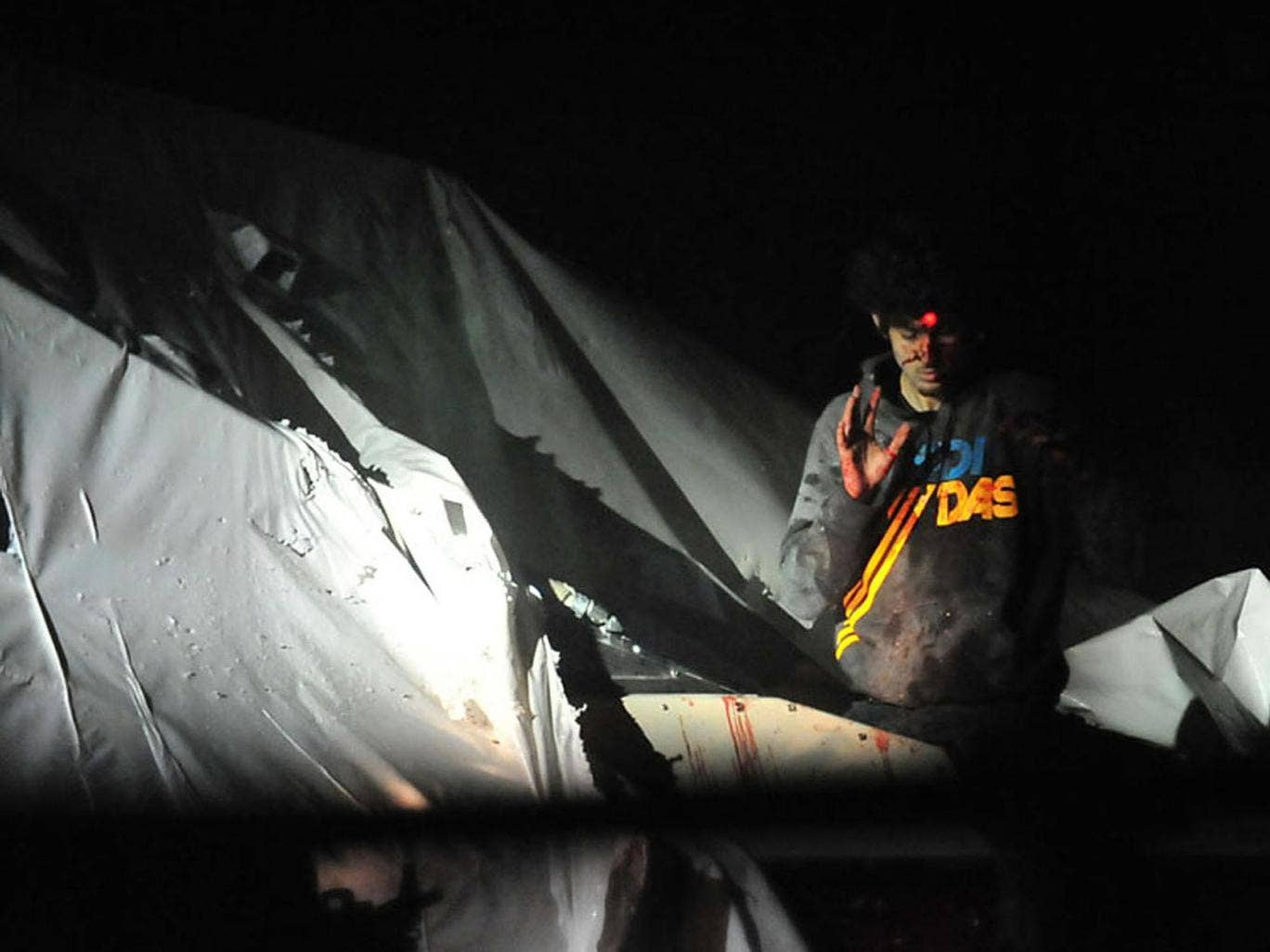 An injured Dzhokhar Tsarnaev emerges from the boat where he had been hiding - a sniper's red dot can be seen on his head