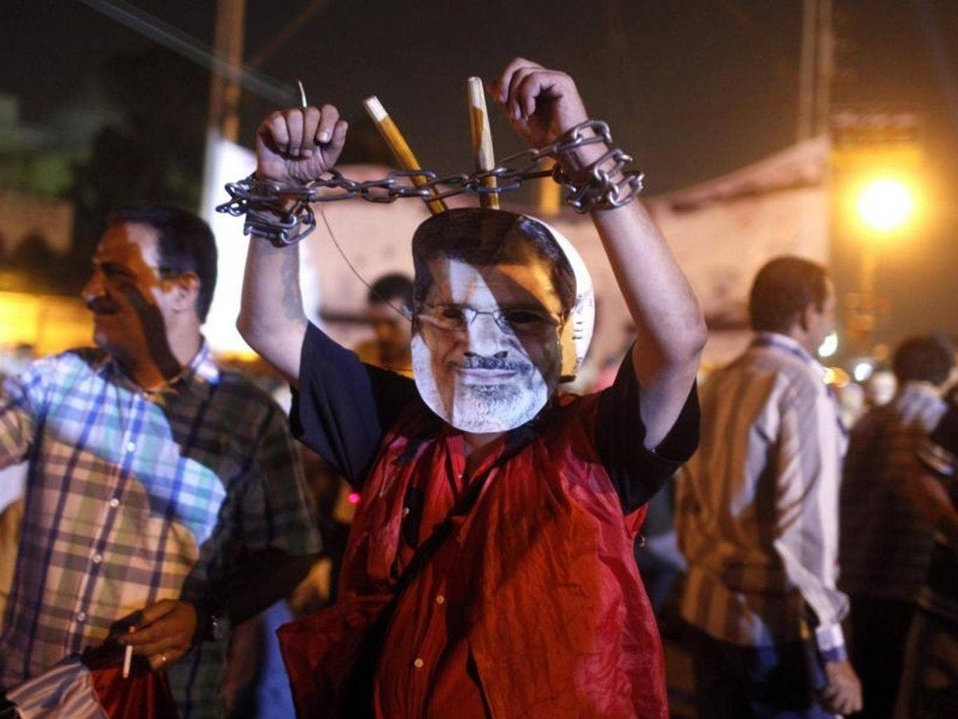 An anti-Morsi protester wears a mask depicting deposed president, and chains on his hands, close to the presidential palace in Cairo
