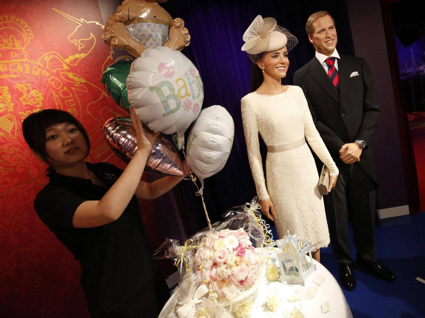 A staff member of the Madame Tussauds Tokyo wax museum prepares decorations next to the wax figures of Britain's Prince William and his wife Catherine