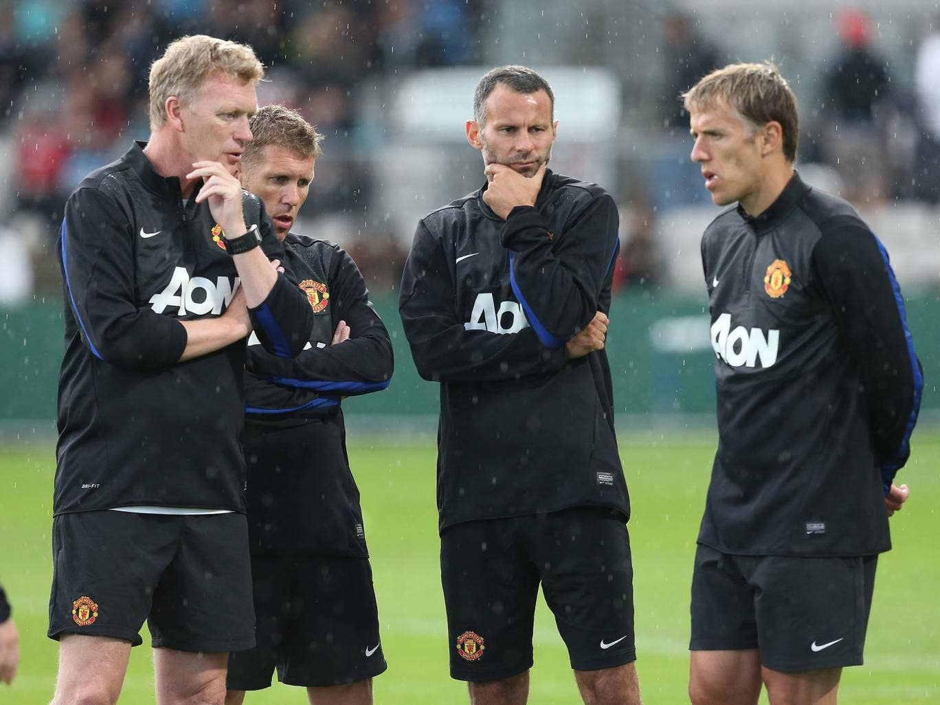 Manager David Moyes of Manchester United speaks to Assistant Manager Steve Round, Ryan Giggs and Coach Phil Neville