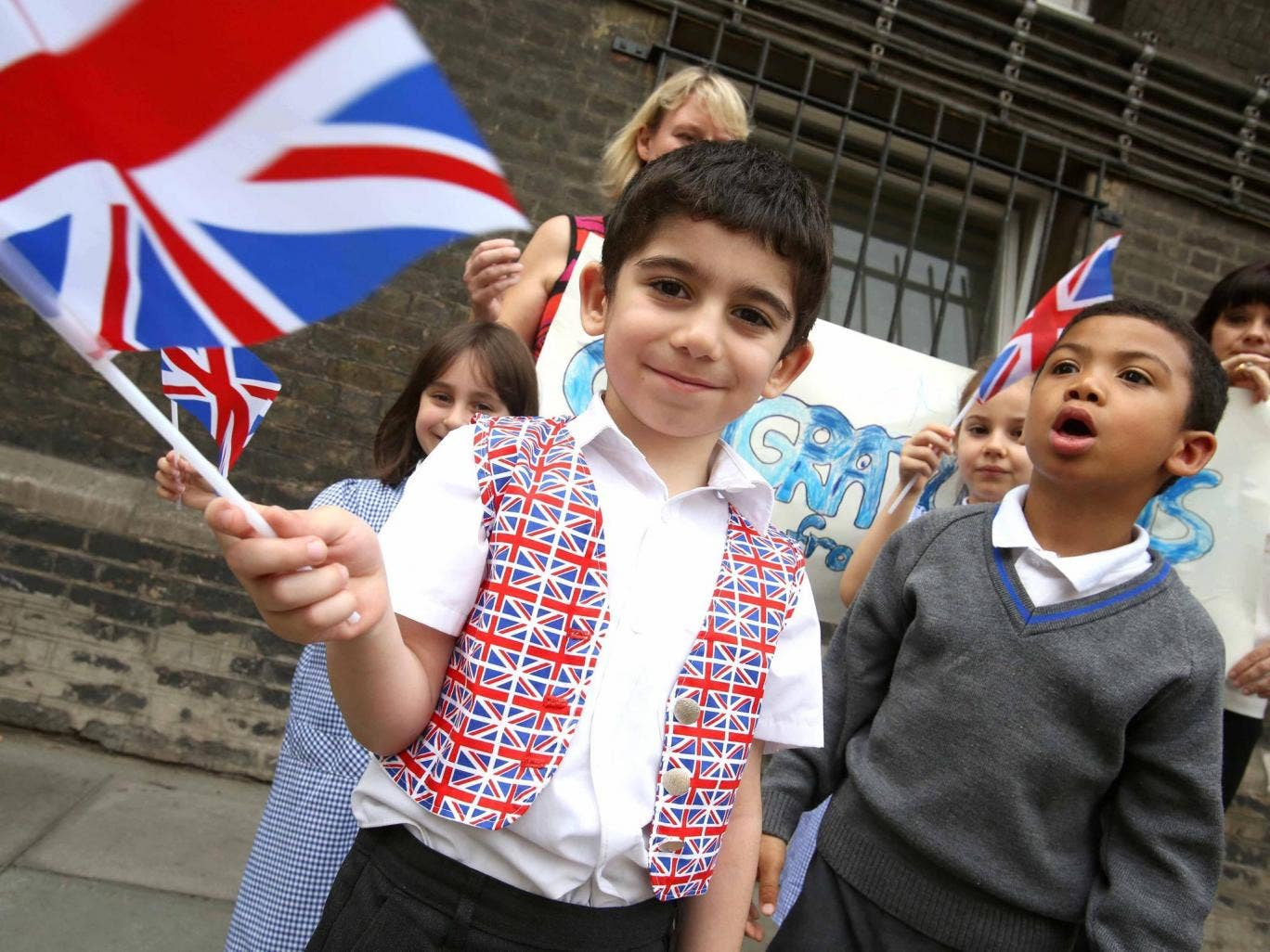 School children wave flags in celebration of the birth of the royal baby outside St. Mary's hospital
