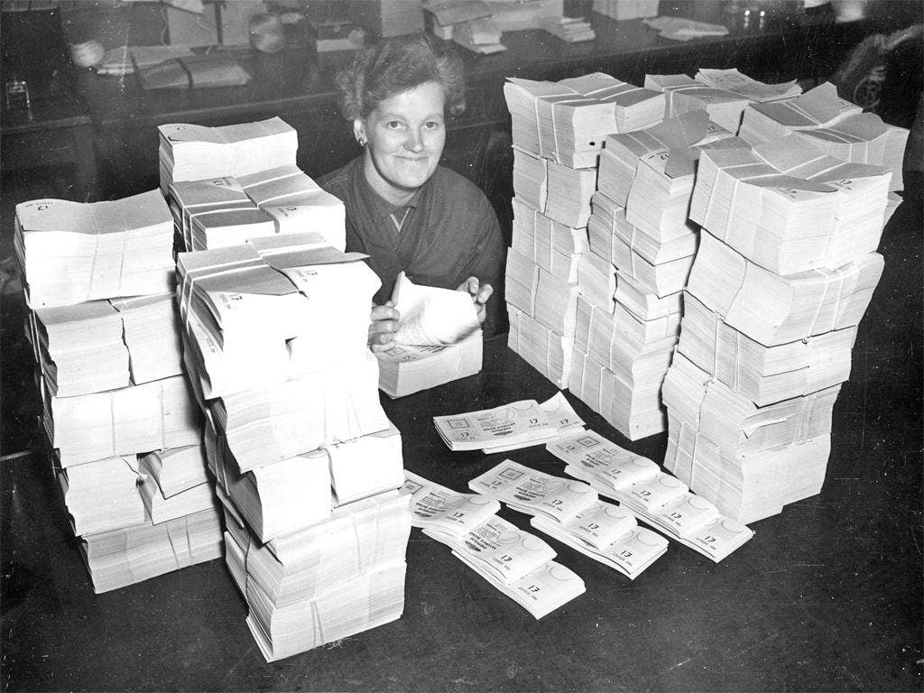 A worker counts one pound denomination premium bonds at a Post Office distribution centre in 1956