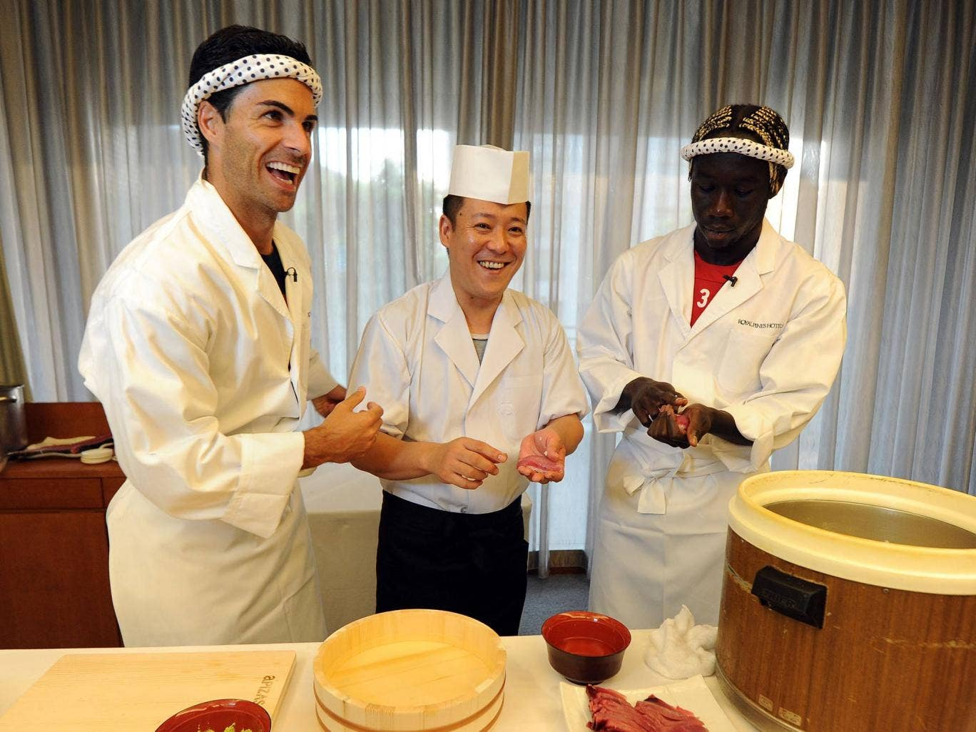 Mikel Arteta (L) and Bacary Sagna (R) of Arsenal FC are given a lesson in making Sushi from a top Sushi Chef in the Urawa Royal Pines Hotel in Japan