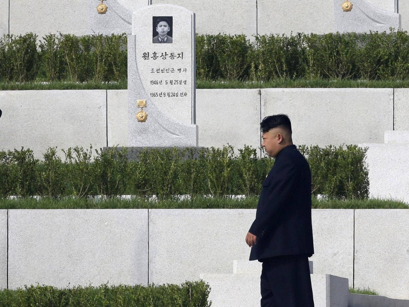 Kim Jong-un walks past tombstones at the opening of the Cemetery of Fallen Fighters in Pyongyang