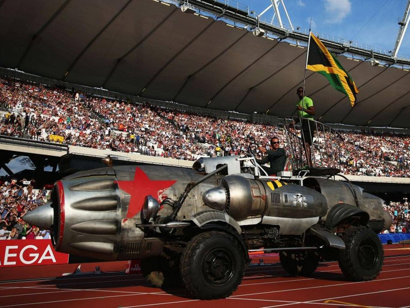 Usain Bolt with a Jamaica flag arrives in the Olympic Stadium in typically flamboyant style aboard a jet engine car