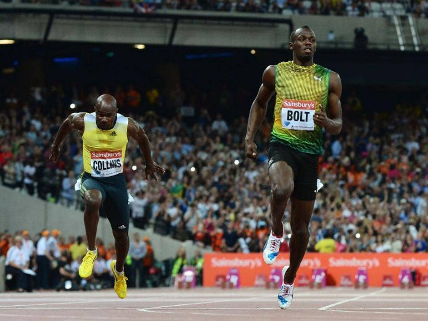 Usain Bolt crosses the line first ahead of Kim Collins