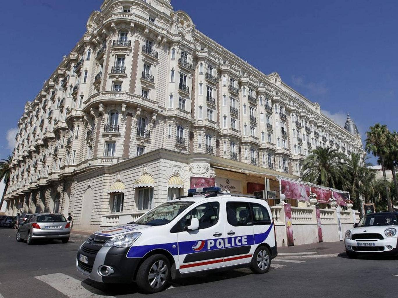 A police car stands outside the Carlton Intercontinental Hotel in Cannes