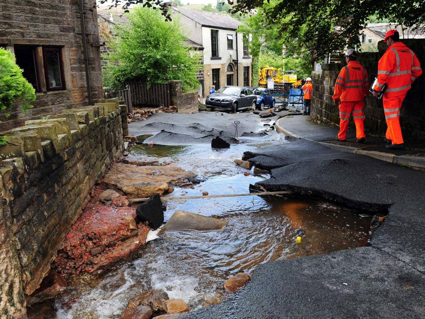 Engineers examine the damage left by flash floods in Walsden, near Todmorden