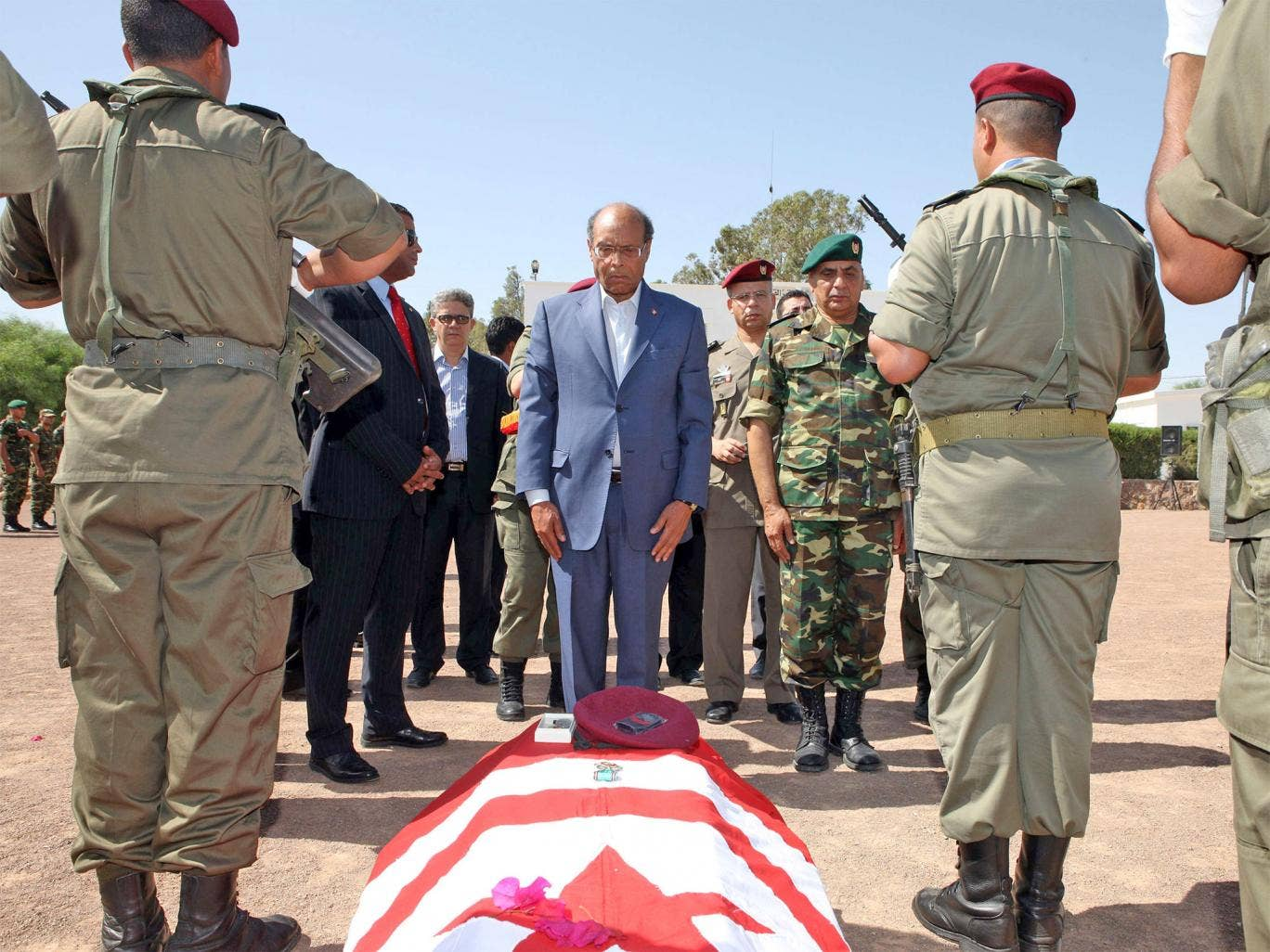 President Moncef Marzouki stands in front of coffin, draped in the Tunisian flag, of the one of the eight soldiers who died in an ambush by an armed group in Mount Chaambi