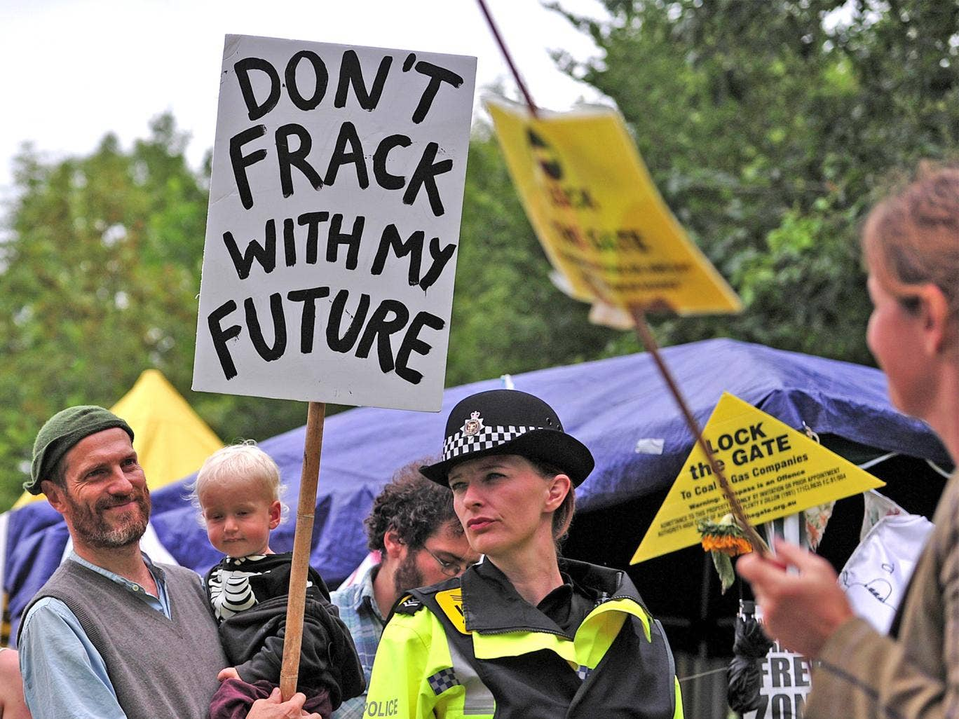 Police monitor protesters standing near to the entrance of the drill site in Balcombe