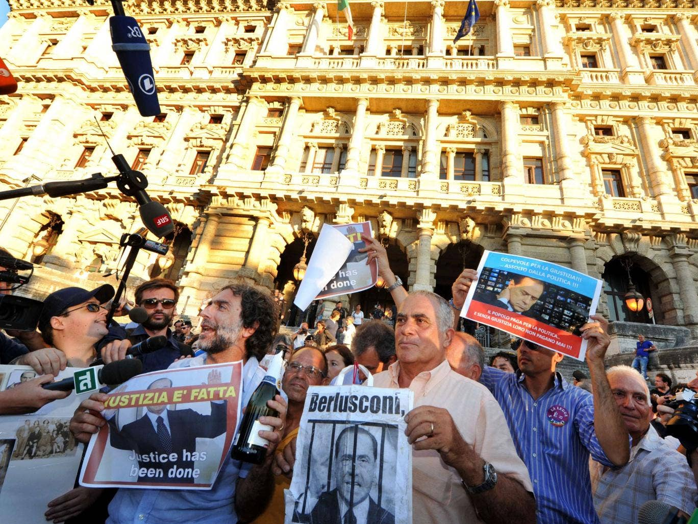People hold signs as they celebrate the Italian Supreme Court's sentencing of Italian politician Silvio Berlusconi, in front of the Cassation building in Rome