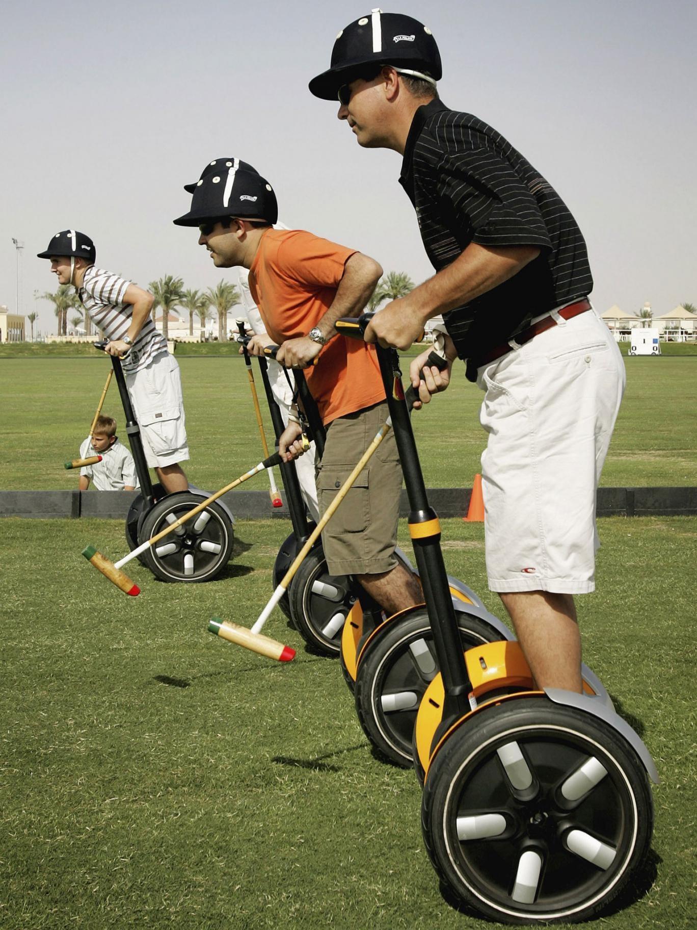 Expatriates play polo on Segway Human Transporters before a charity polo match at Dubai Polo Club