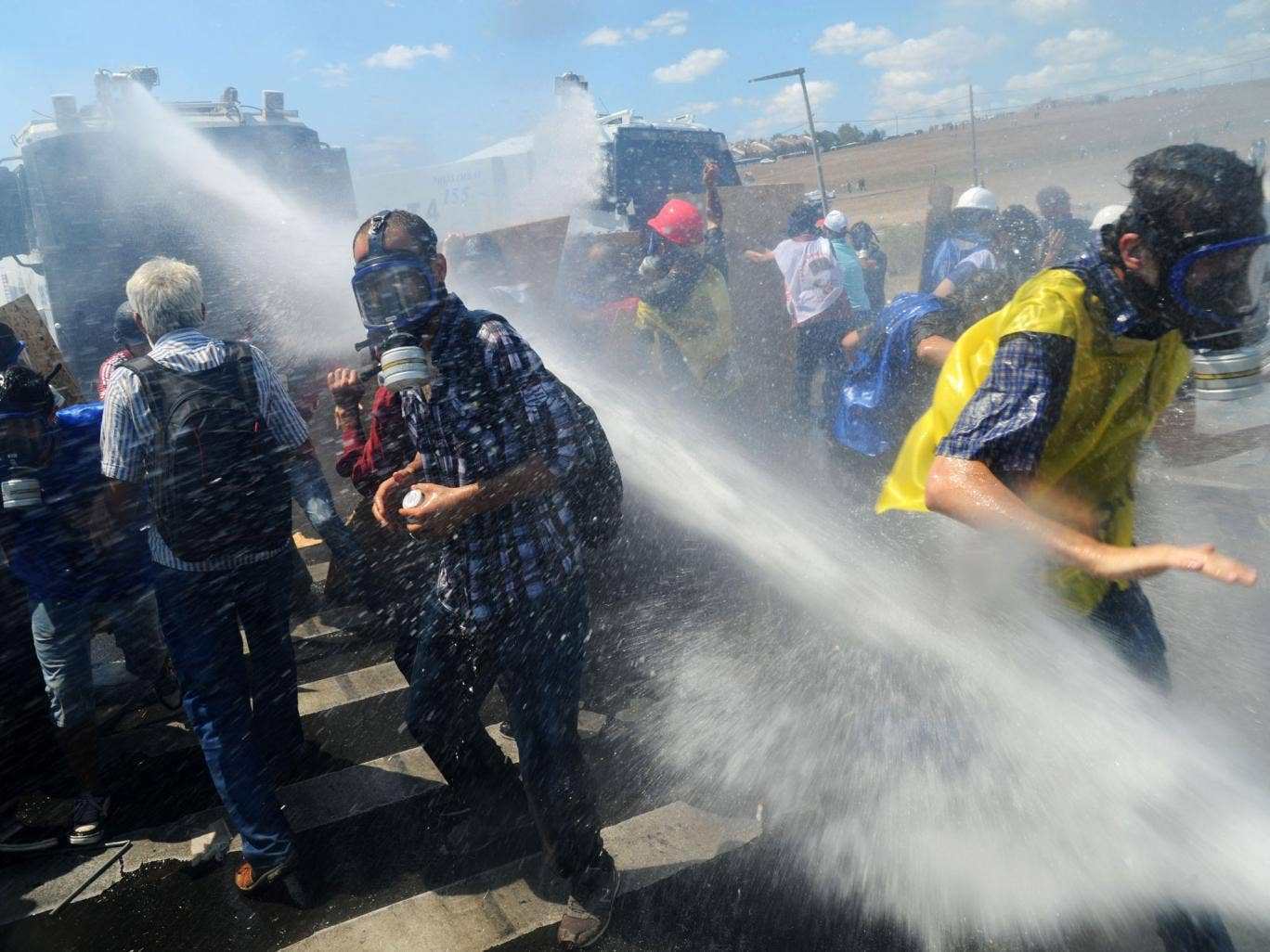 Demonstrators are hit by water cannon during clashes against Turkish police forces