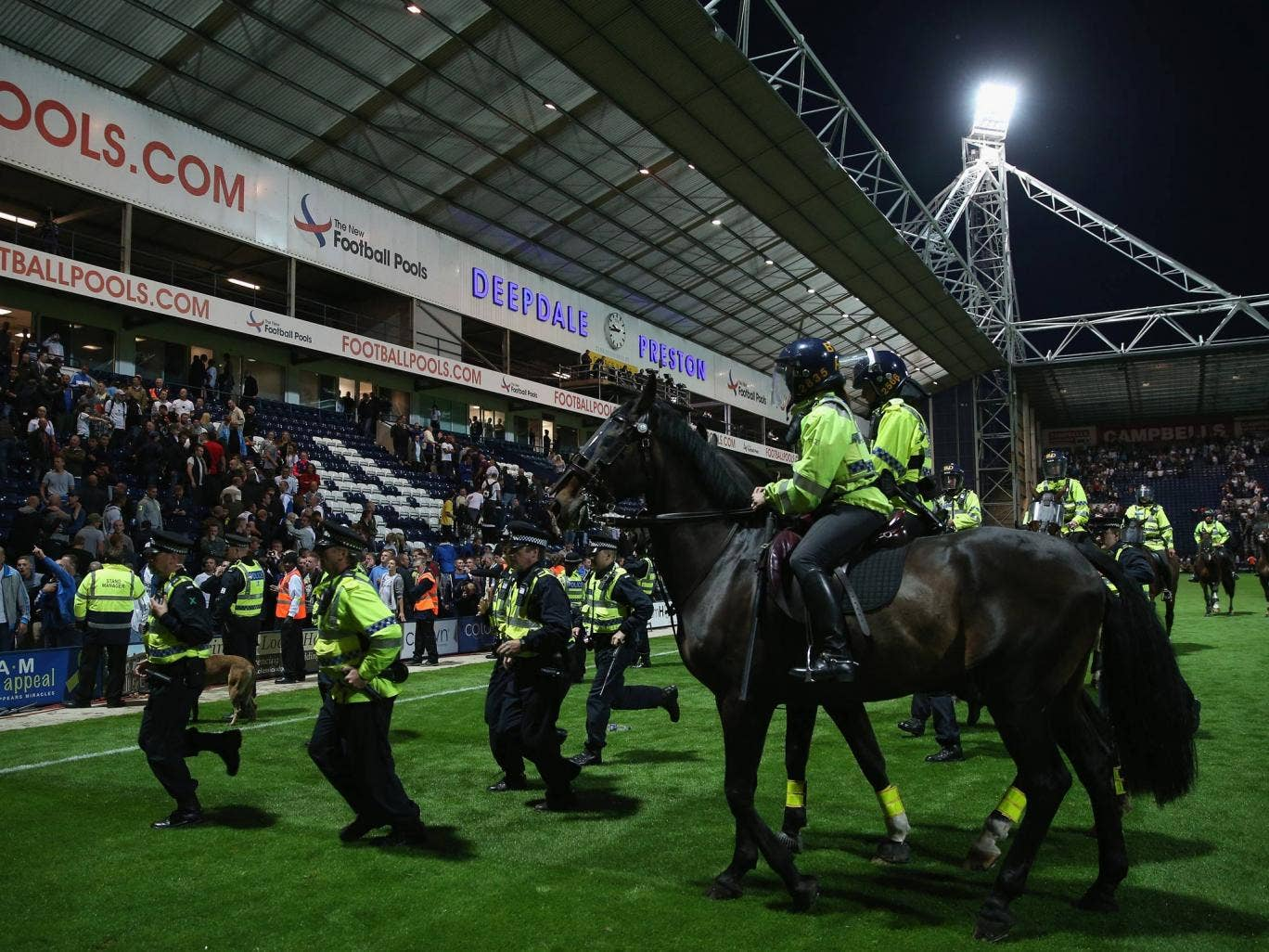 Police on foot and horse try to control the pitch invasion by fans at the final whistle of the Capital One Cup first round match between Preston North End and Blackpool
