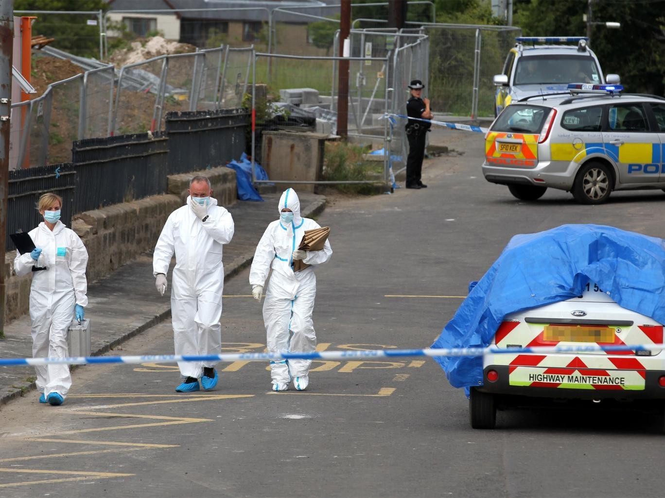 Police forensics examine the scene on Auldhouse main street