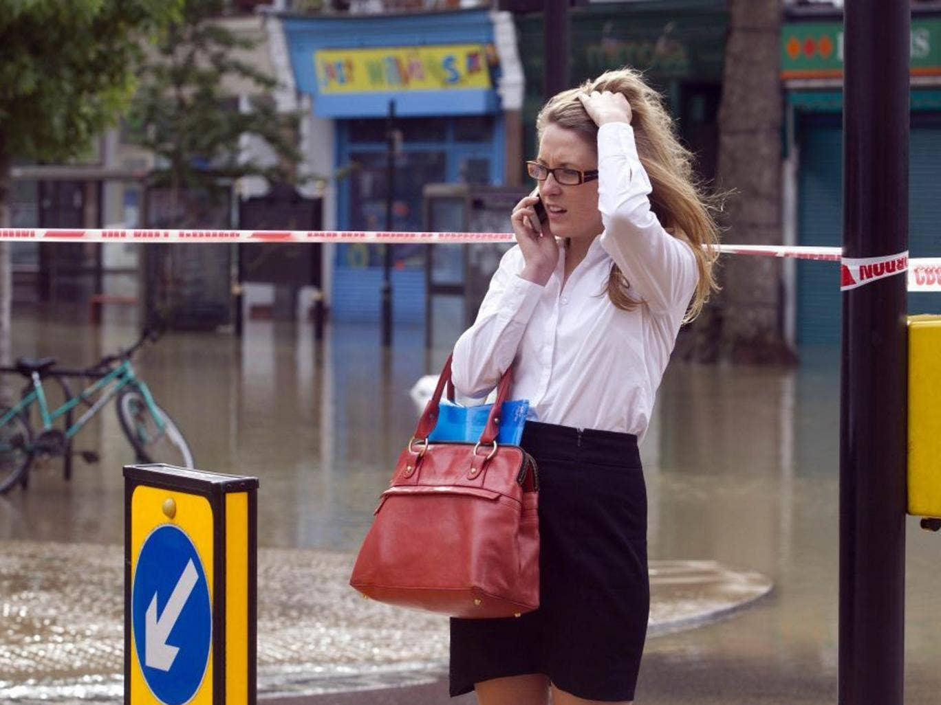 A woman on her phone at Half Moon Lane in Herne Hill, London as a burst water main has resulted in severe flooding