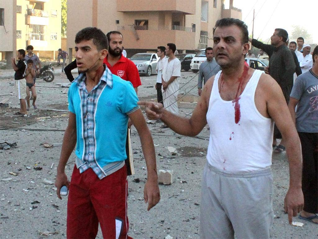 Injured men walk away from the scene of an explosion in the northern Syrian city of Raqqa