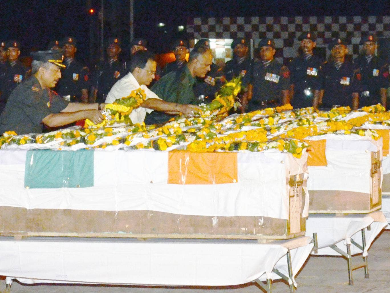 Indian Army officers lay wreaths and pay their respects over the caskets of five soldiers killed in during a cross-border attack in Kashmir, following the arrival of their remains at the Patna Airport