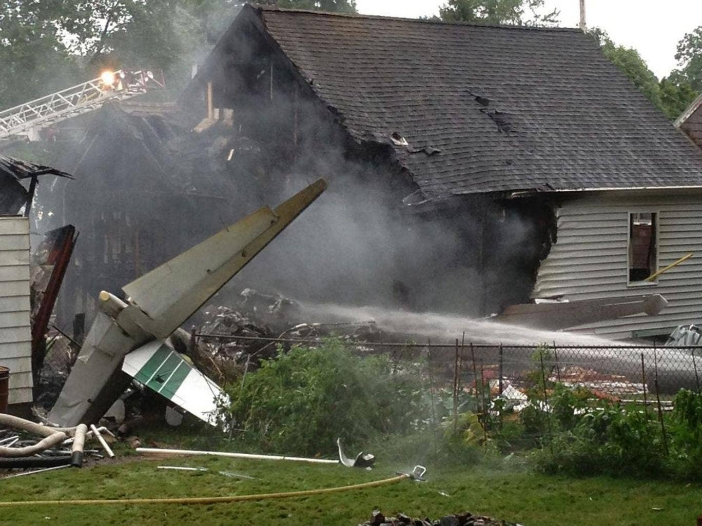 The tail of a small aircraft sits behind a burned home following a crash in East Haven, Connecticut
