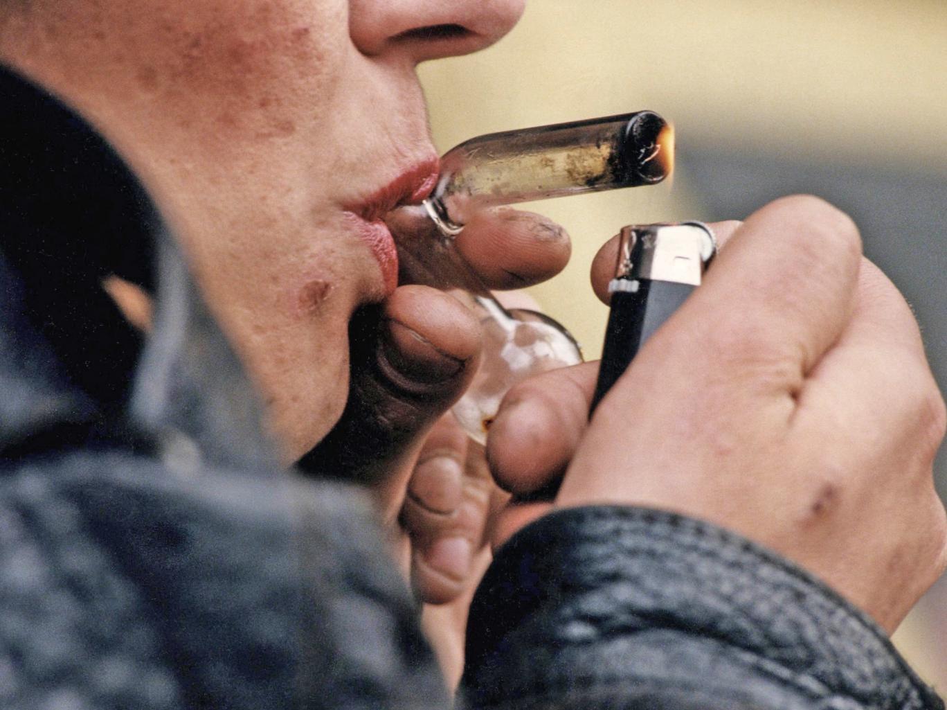 A drug addict smoking a crack pipe